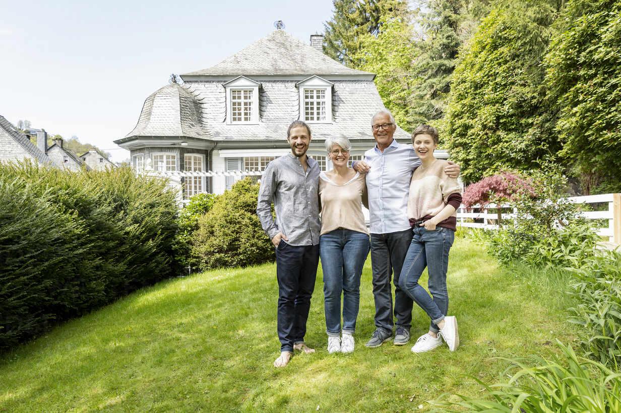 Happy senior couple with adult children standing in garden of their home - MJFKF00126 - MiJo/Westend61