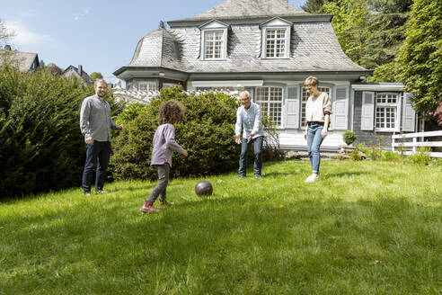 Happy extended family playing football in garden - MJFKF00132