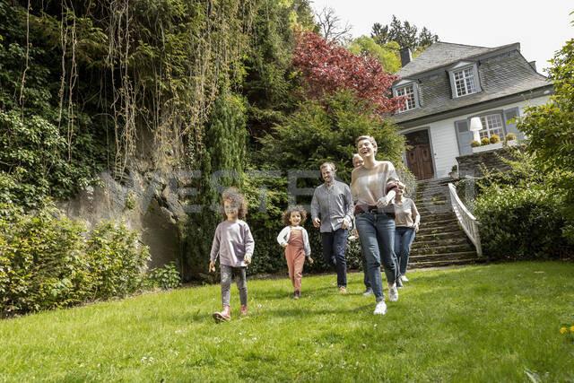 Happy extended family walking in garden of their home - MJFKF00138 - MiJo/Westend61