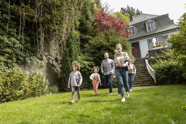 Happy extended family walking in garden of their home - MJFKF00138