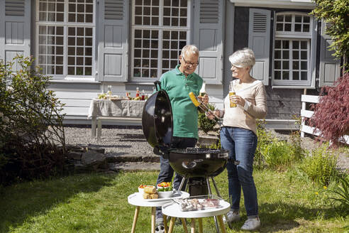 Happy senior couple having a barbecue in garden of their home - MJFKF00141
