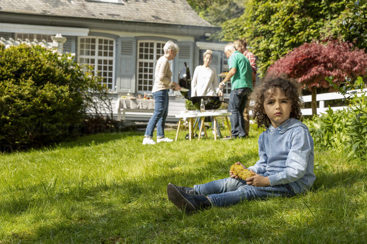 Boy with corn cob on a family barbecue in garden - MJFKF00144 - MiJo/Westend61