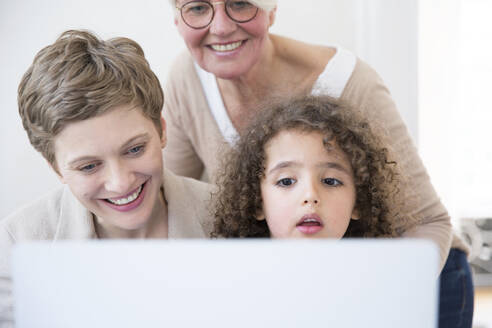 Smiling grandmother, mother and son using laptop at home - MJFKF00147