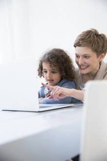 Smiling mother and son using laptop at home - MJFKF00150