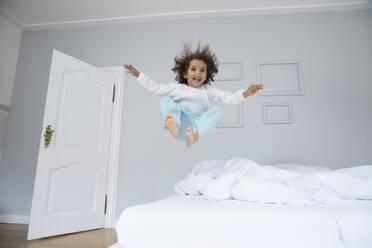 Playful boy bouncing in bed - MJFKF00153