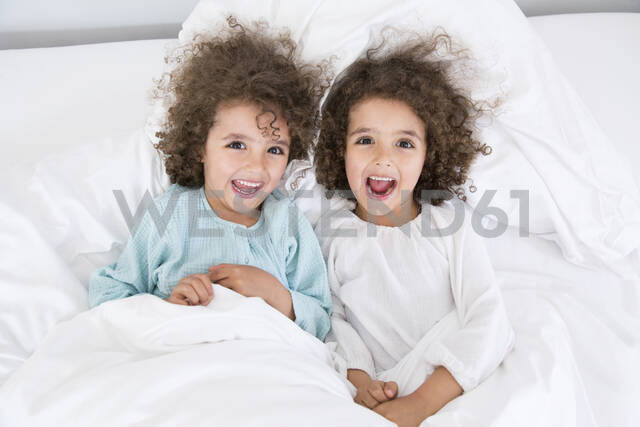 Portrait of two happy twin brothers lying in bed - MJFKF00162 - MiJo/Westend61