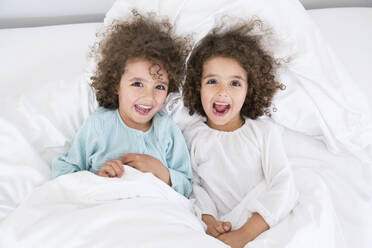 Portrait of two happy twin brothers lying in bed - MJFKF00162