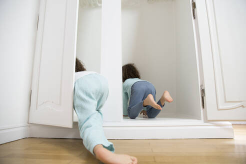 Two twin brothers crawling into wardrobe at home - MJFKF00165