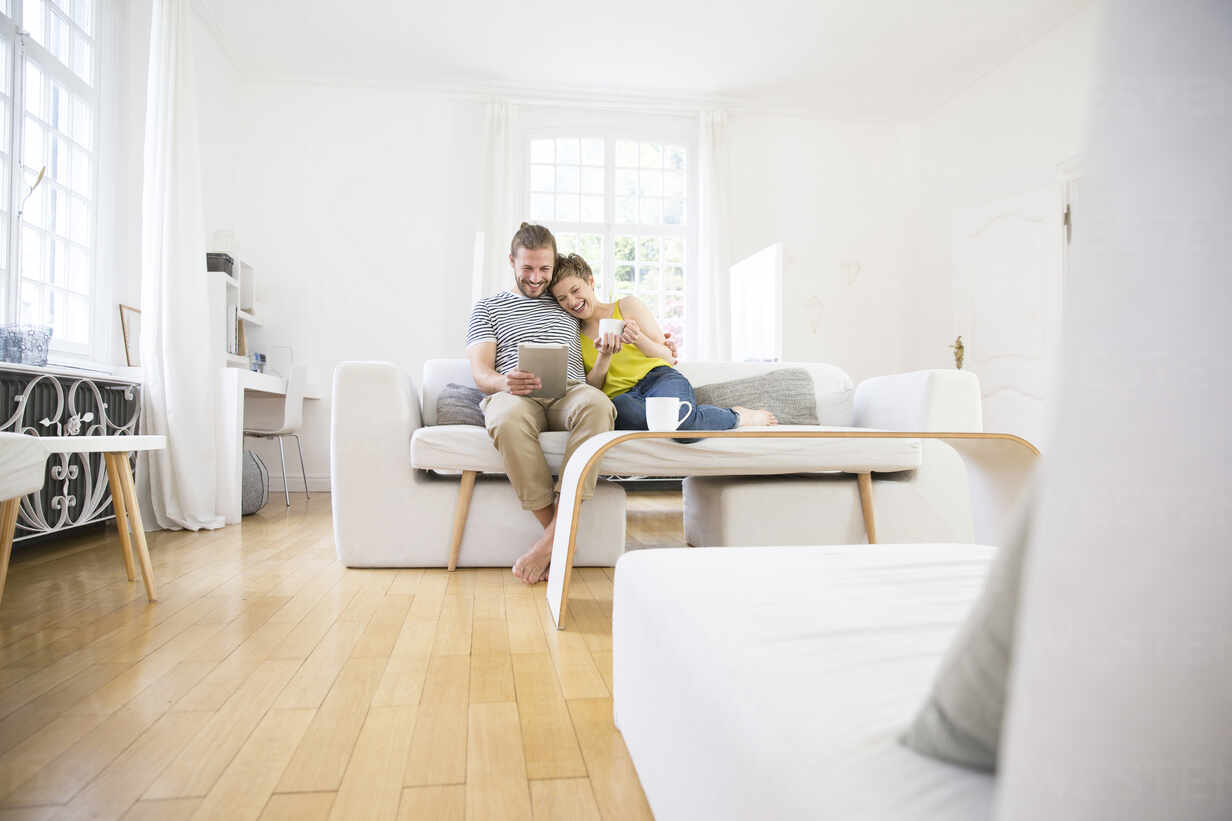 Happy young couple using tablet on couch at home - MJFKF00174 - MiJo/Westend61
