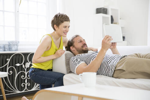 Happy young couple with tablet in living room at home - MJFKF00177