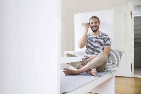Smiling young man using smartphone at home - MJFKF00183