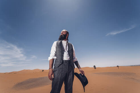 Man with a beard and hat in the dunes of the desert of Morocco - OCMF00711