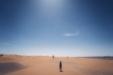 Lonely man with hat standing in the dunes of the desert of Morocco - OCMF00714