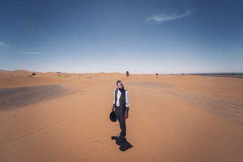 Man with a beard and hat in the dunes of the desert of Morocco - OCMF00717