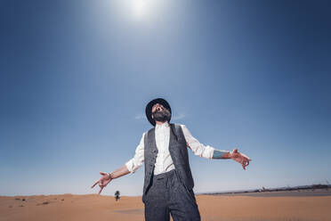 Man with a beard and hat screaming in the dunes of the desert of Morocco - OCMF00720