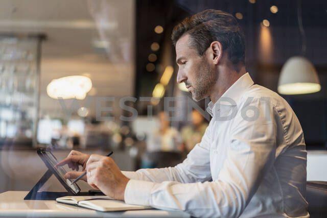 Businessman using tablet and taking notes in a cafe - DIGF08400 - Daniel Ingold/Westend61
