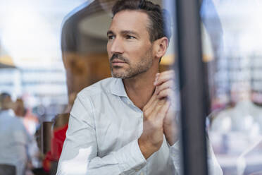 Portrait of businessman behind windowpane in a cafe - DIGF08409
