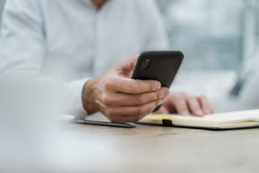 Close-up of businessman with notebook and cell phone - DIGF08412