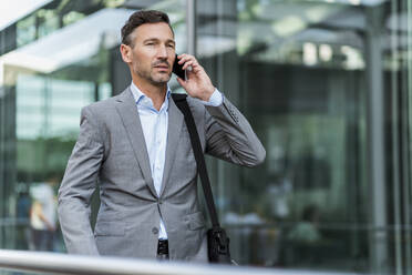 Businessman on cell phone in the city - DIGF08424