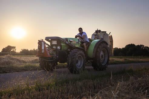 Organic farmer on a tractor at sunset - SEBF00207