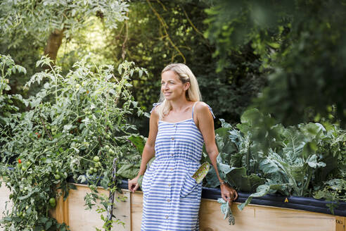 Blond woman standing in front of her raised bed in her own garden - HMEF00504