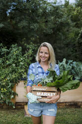 Blond woman with wooden box and organic vegetables - HMEF00531