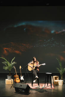 Female musician playing guitar on stage - HEROF38590