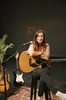 Portrait confident female musician with tattoos holding guitar on stage - HEROF38593