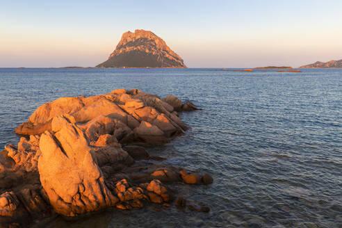 Sun illuminates rocks with Tavolara Island in the background at sunset, Loiri Porto San Paolo, Olbia Tempio province, Sardinia, Italy, Mediterranean, Europe - RHPLF09730