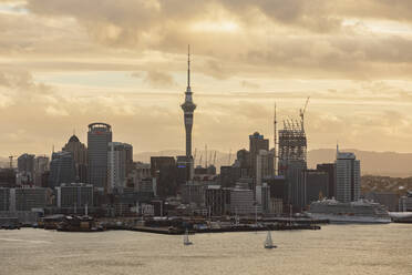 Modern buildings by sea against cloudy sky during sunset, Oceania, New Zealand - FOF10884