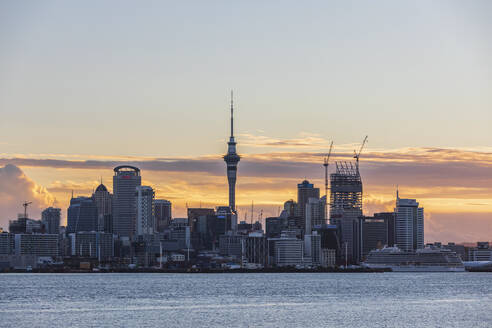 Modern buildings by sea against cloudy sky at sunset, Oceania, New Zealand - FOF10887