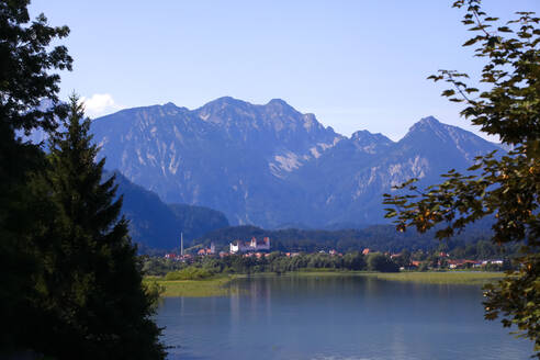 Scenic view of Forggensee lake and mountains against blue sky at Fussen, Germany - JTF01336