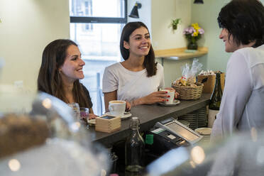 Two happy young female friends at the counter in a cafe - GIOF07079