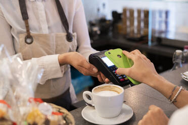 Close-up of customer paying cashless with smartphone in a cafe - GIOF07082