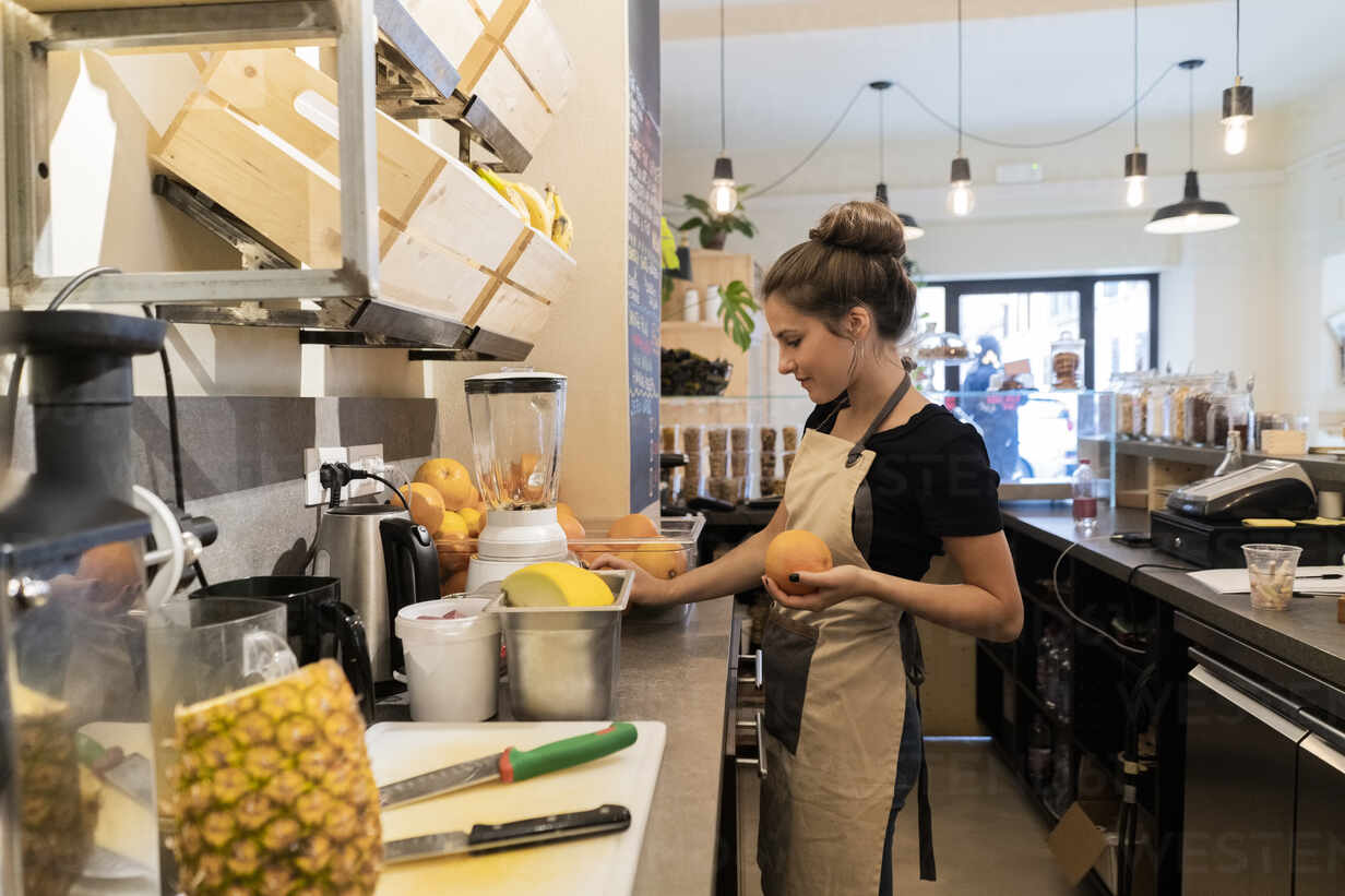 Young woman working in a cafe preparing a fresh drink - GIOF07100 - Giorgio Fochesato/Westend61