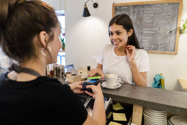 Customer paying cashless with smartphone in a cafe - GIOF07103