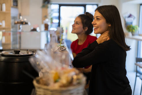 Two smiling young women at the counter in a cafe - GIOF07139