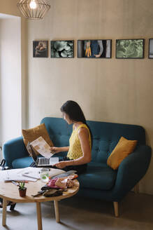 Fashion designer sitting on couch checking color samples - ALBF01133