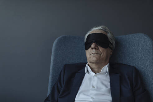 Senior businessman sitting in armchair wearing eye mask - GUSF02534