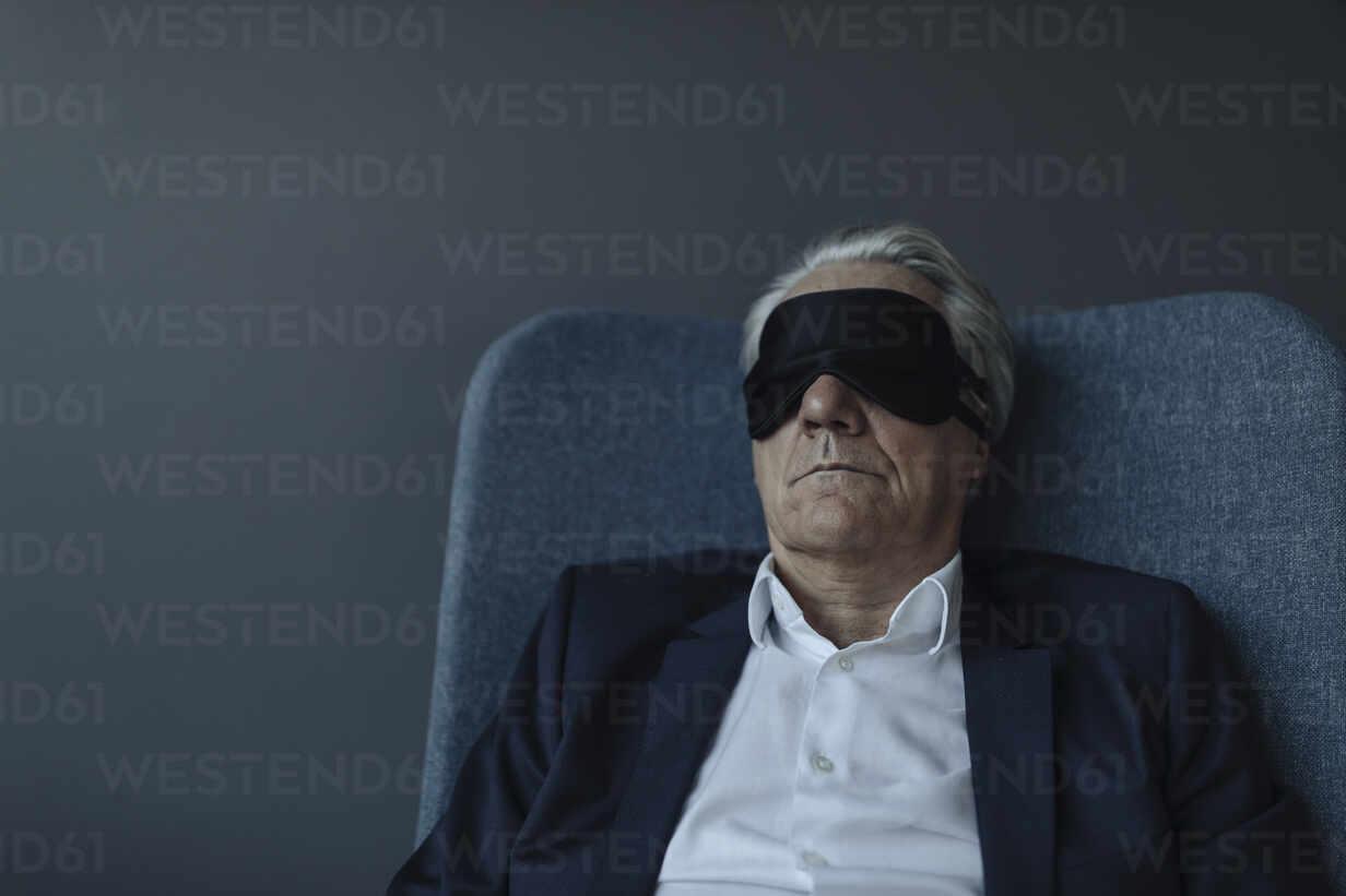 Senior businessman sitting in armchair wearing eye mask - GUSF02534 - Gustafsson/Westend61