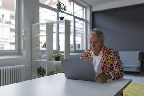 Senior businessman wearing colorful sports jacket using laptop - GUSF02540