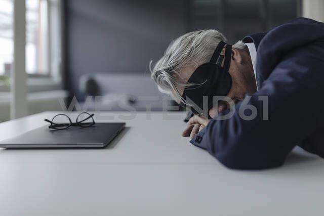 Senior businessman wearing eye mask lying on desk - GUSF02546 - Gustafsson/Westend61