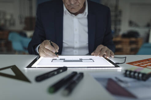 Close-up of senior businessman drawing on shining tablet - GUSF02561