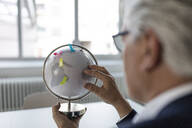 Senior businessman looking at globe with post its - GUSF02564