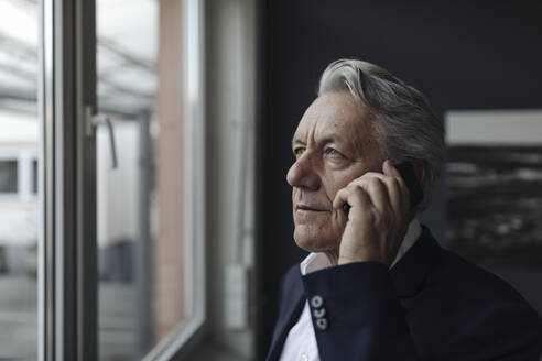 Portrait of a senior businessman talking on cell phone at the window - GUSF02576