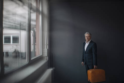 Senior businessman holding old-fashioned suitcase - GUSF02585