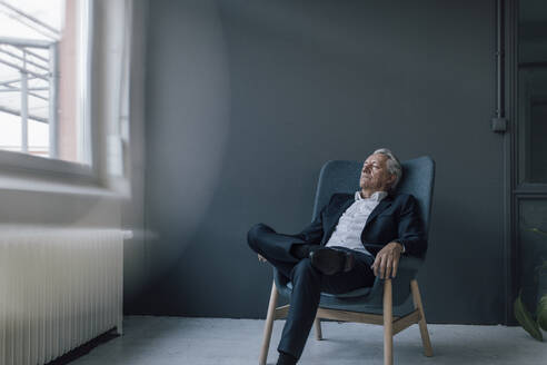 Senior businessman sitting in armchair with closed eyes - GUSF02615