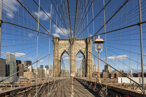 Diminishing perspective of Brooklyn Bridge against blue sky in New York City, USA - XCF00215