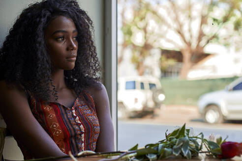 Portrait of young African woman with flowers on the table in a cafe, looking out of window - VEGF00690