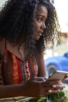 Young African woman checking her phone. Lubango, Angola. - VEGF00693